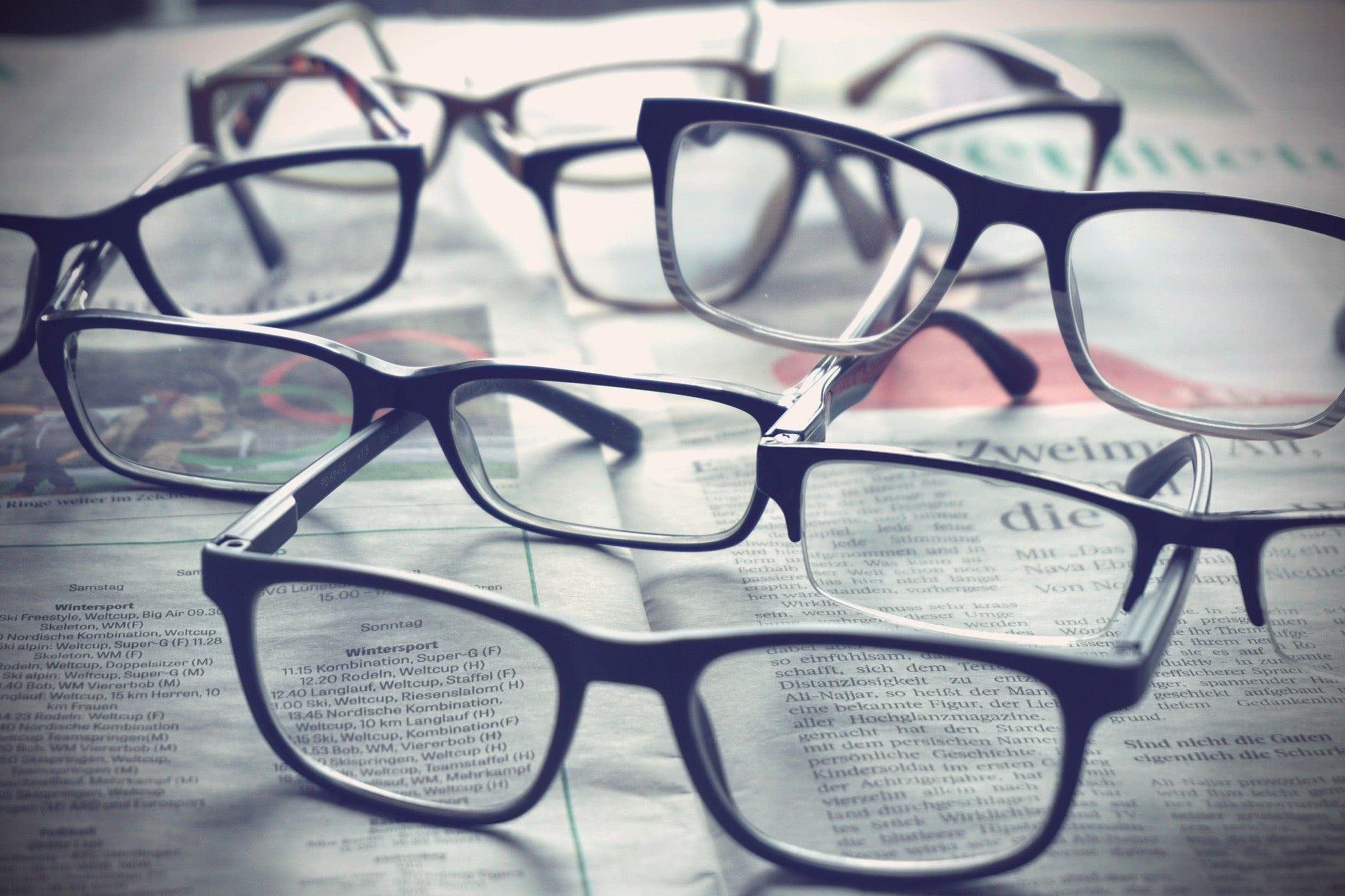 Foto: Zahlreiche Brillen, die auf Zeitungen liegen