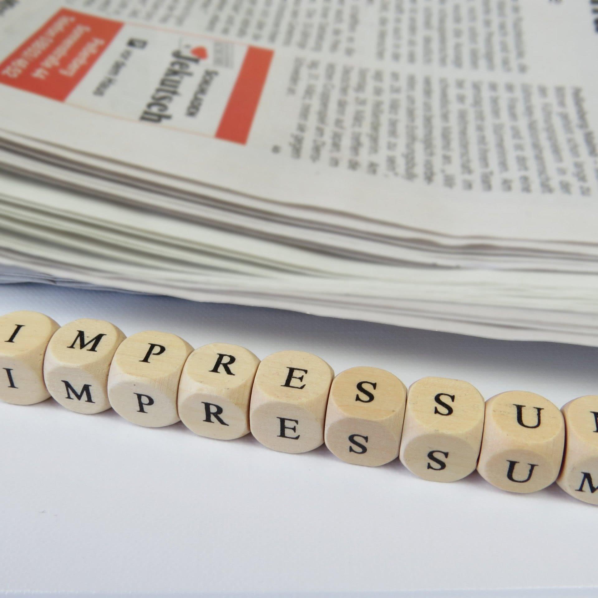 Foto: Buchstaben-Würfel, welche das Wort «IMPRESSUM» bilden