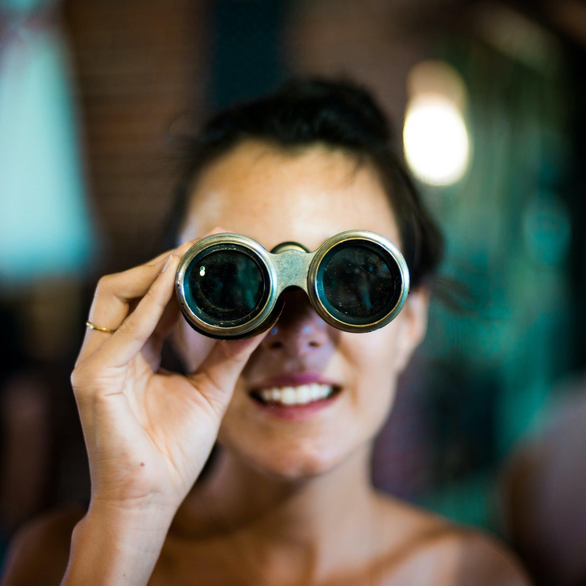 Foto: Frau, die ein Fernglas hält