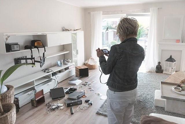 Frau dokumentiert die Spuren eines Einbruchdiebstahls mit ihrer Fotokamera