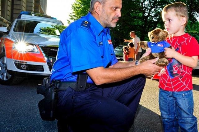 Polizist überreicht einem Buben einen Plüsch-Polizeibären