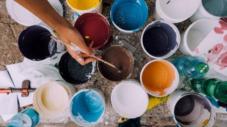 Eine Frau mit einem Pinsel und vielen Farbtöpfen streicht eine Wand