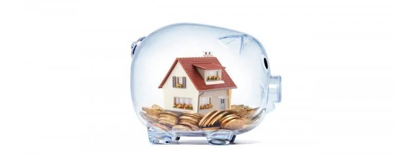 Sparschwein mit Haus und Geldmünzen